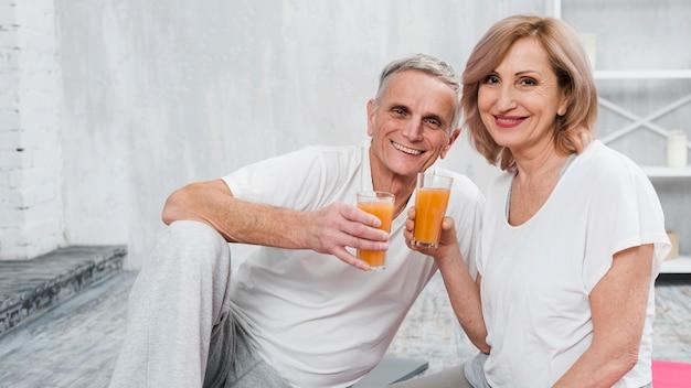 自宅で座って幸せな老夫婦ジュースのガラスを保持