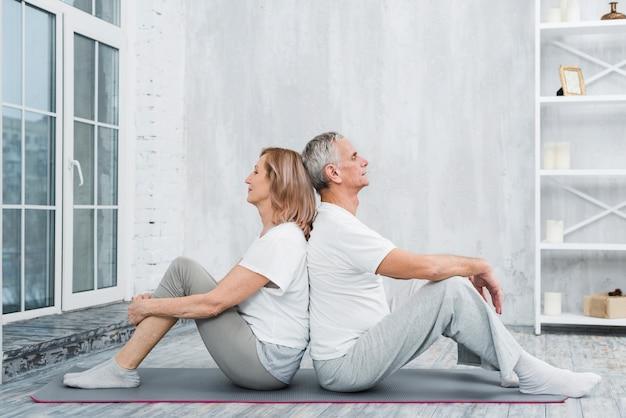 リビングルームで運動後休んで年配のカップル
