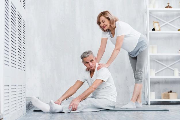 うれしそうな年配のカップルが自宅で運動しながら楽しんで