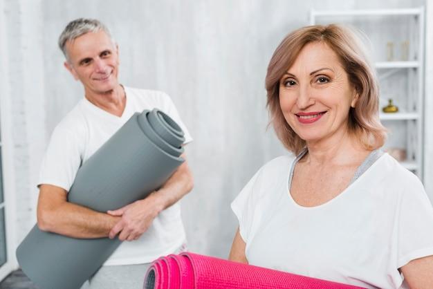 彼の笑顔の妻を見てマットを保持している陽気な年配の男性