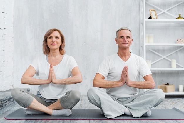ロータスに座っている年配の家族カップルは灰色のヨガマットの上ポーズします。