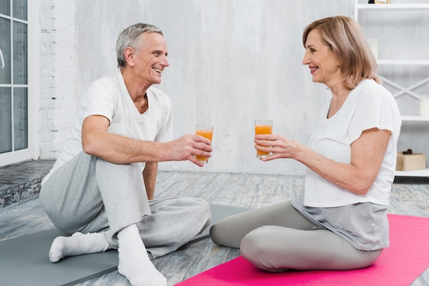 陽気なカップルがヨガをやった後フルーツジュースを楽しむ