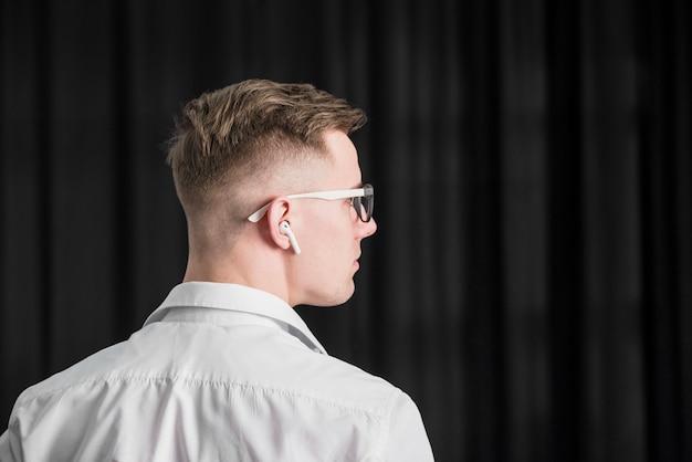 彼の耳にワイヤレスイヤホンと眼鏡を身に着けている若い男の背面図