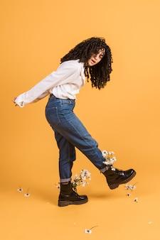 Женщина с цветами в сапогах поднимает ногу