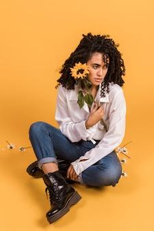 Женщина с цветком сидит на полу