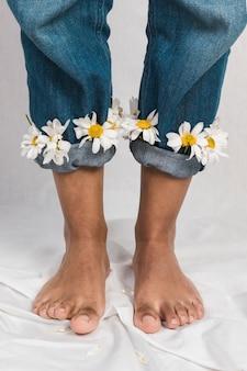 Чернокожая женщина с цветами ромашки в джинсовых манжетах