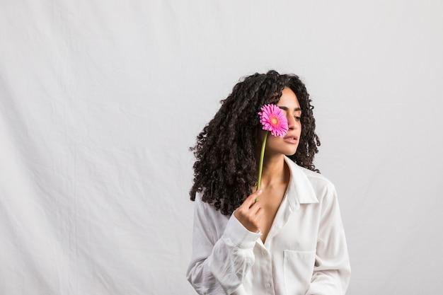 Черная женщина, держащая герберы на лице