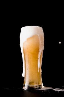黒の背景の前にビールのグラス