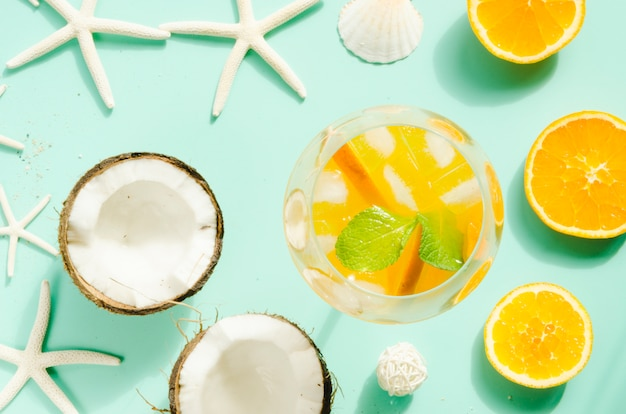 Коктейль с апельсином, мятой и льдом рядом с кокосами