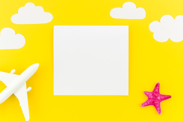 Маленькая игрушка самолет с облаками и чистый лист бумаги