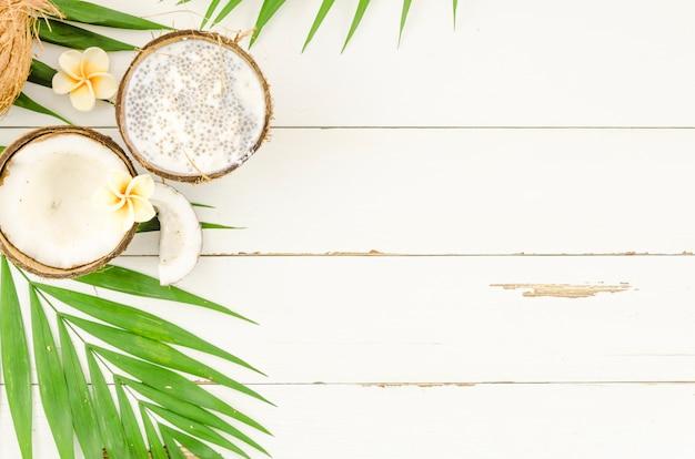 木製のテーブルにココナッツと緑のヤシの葉