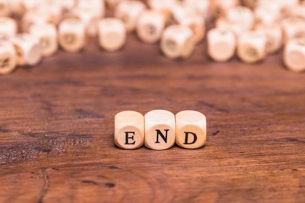 デスク上の単語の終わりを持つ木製キューブ