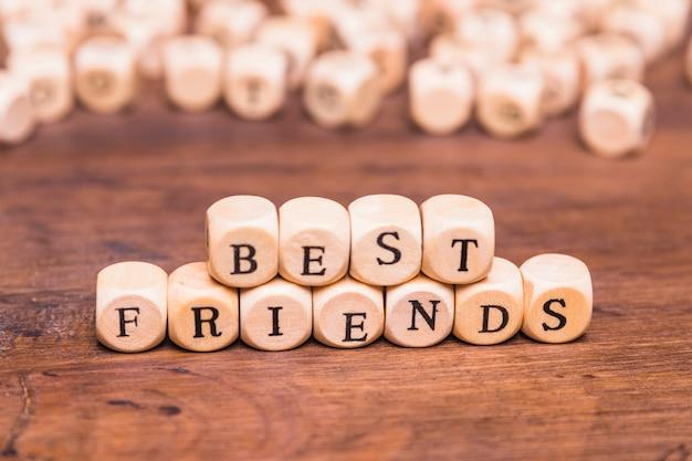 机の上の木製のサイコロと親友の言葉