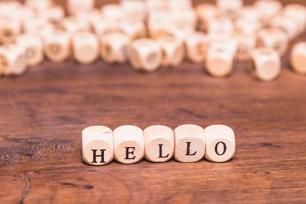 こんにちは木製の机の上のサイコロで作られた言葉