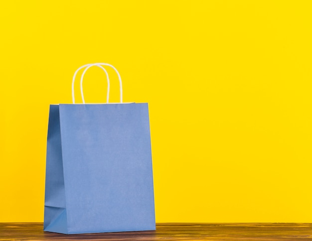 黄色の背景と木の表面に青い単一紙袋
