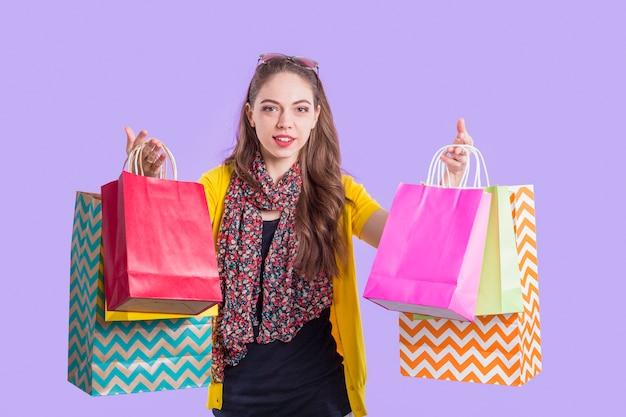 カラフルな紙の袋を示すスタイリッシュな女性の笑みを浮かべてください。