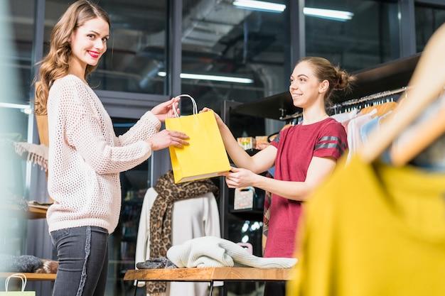 Владелец бутика дает желтую бумажную сумку улыбающейся молодой женщине