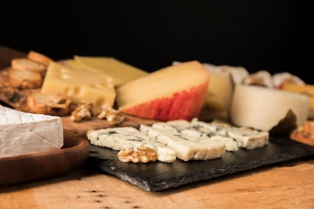 チーズとクルミの木製のテーブルの上のクローズアップ