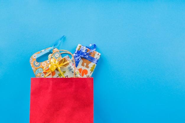 Упакованный подарок в красной сумке для покупок на простом фоне