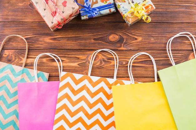 木の表面の上に包まれたギフトと装飾的な紙の買い物袋