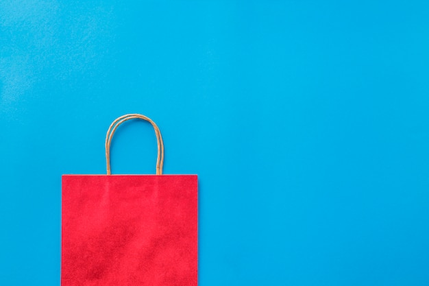青い背景の空の赤い買い物袋