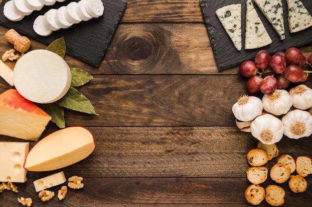 チーズと古い木製の背景上の成分の種類