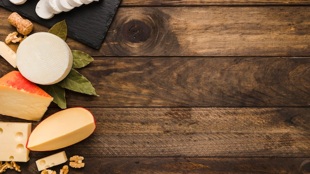 Разнообразный вкусный сыр с лавровым листом и грецким орехом на деревянной фактуре