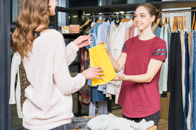 Женский продавец, давая желтую сумку для покупок женщине