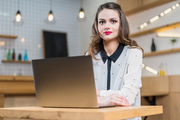 木製のテーブルの上のノートパソコンの前に座っているきれいな女性の肖像画