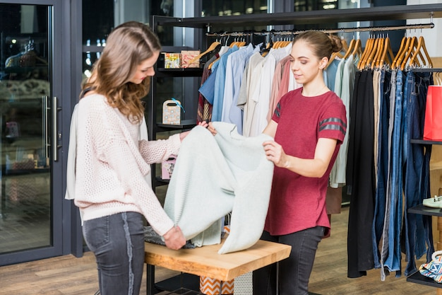 ショッピングセンターで顧客に服を見せる若いコンサルタント