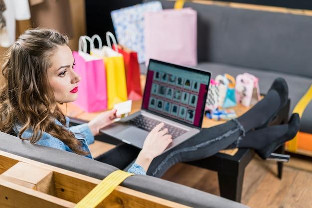 Женщина смотря отсутствующий сидеть с хозяйственными сумками компьтер-книжкой и дебетовой картой