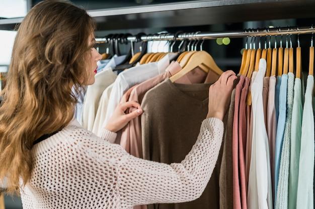 Вид сзади женщины, глядя на одежду на стойке в выставочном зале