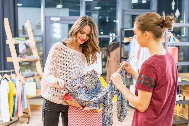 Консультант показывает одежду женскому покупателю в торговом центре