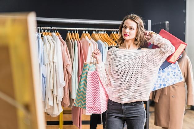 Стильная молодая женщина, стоя в магазине, холдинг сумок