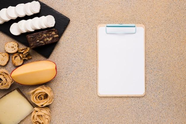 Яркие кусочки сыра; ломтик хлеба; шарики грецкого ореха и макарон возле пустой бумаги в буфер обмена на простой фон