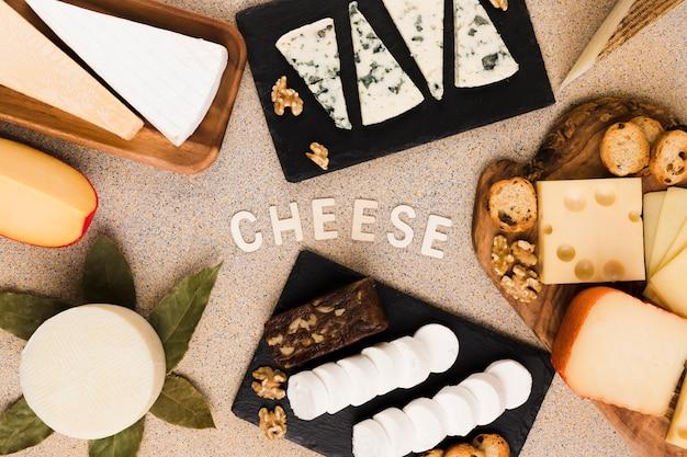 Текст сыра окружен различными кусочками сыра; орех и лавровый лист на текстурированной поверхности