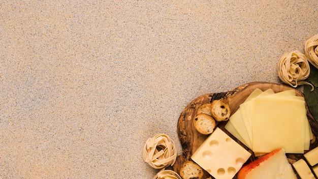 Виды сыров на деревянной подставке с шариками из сырых макарон на углу текстурированной поверхности