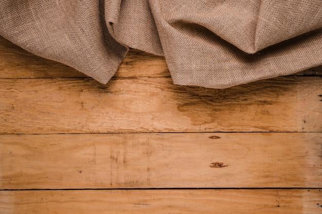 木製のテーブルの背景に黄麻布の質感