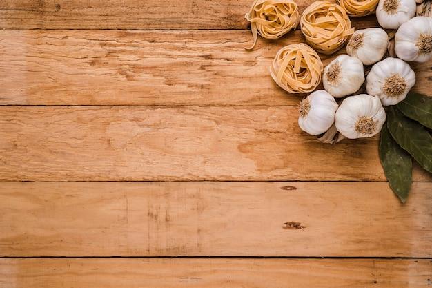 ローリエの葉;ニンニクの球根とテキスト用のスペースを持つ古い織り目加工の壁紙に生パスタ