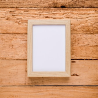 Вид сверху на пустую рамку над текстурированным столом