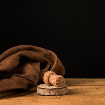 Старая пробка и деревянные подставки возле коричневой ткани над деревянной поверхностью