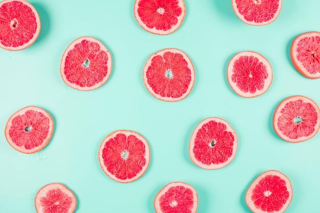 グレープフルーツの柑橘類のスライスのパステル調の背景にスライス