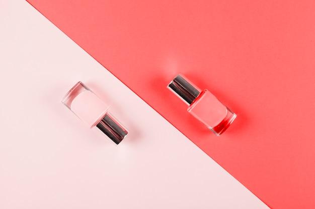 Бутылки лака для ногтей на розовом и коралловом диагональном фоне