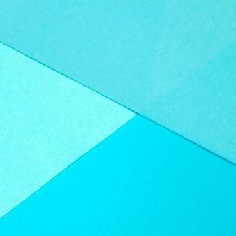 青い紙の幾何学的なフラットレイアウトの背景色