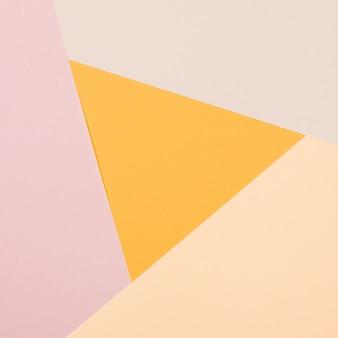 カラフルな紙の幾何学的なフラットレイアウトの背景を持つ黄色の三角形
