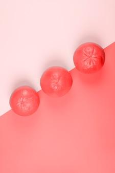 Три целых коралловых грейпфрута на диагональном фоне