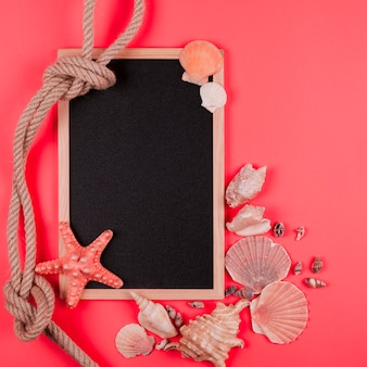 結ばれたロープとサンゴの背景に空白の黒板と貝殻