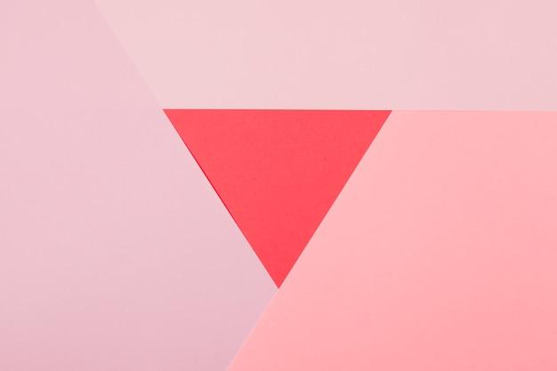 ピンクの紙の背景に囲まれた赤い三角形