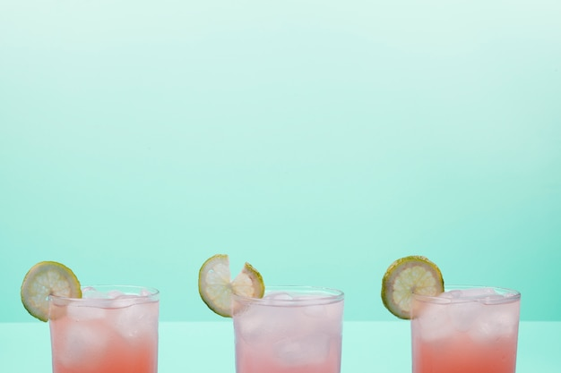 レモンスライスとミントの背景に対してアイスキューブとカクテルのグラス