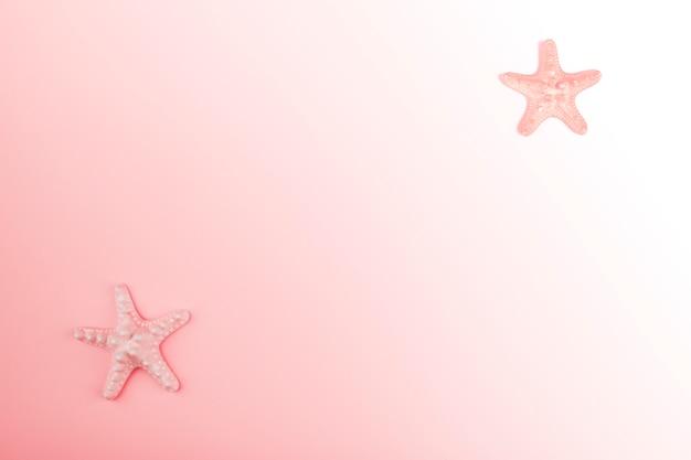 ピンクのグラデーションの背景の角にヒトデ